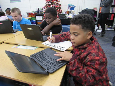 CATHY SPAULDING/Muskogee Phoenix New Tech at Cherokee Elementary fifth-graders, from left, Joshua Jimerson, Daquan Jones and Marcus White use laptops to work on projects. Cherokee is incorporating project-based learning in its program this year.