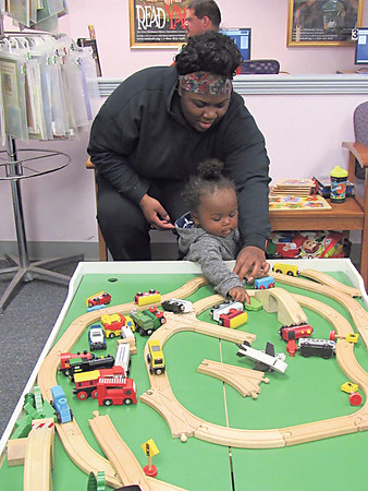 CATHY SPAULDING/Muskogee Phoenix Leeandra Thompson helps 1-year-old Kaidaiah Thompson play with a wooden train track Thursday afternoon at Q.B. Boydstun Library in Fort Gibson. Showers sent many people indoors for fun.