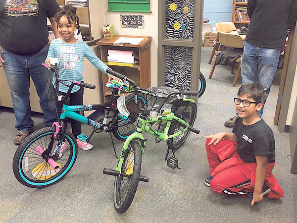 """CHESLEY OXENDINE/Muskogee Phoenix Ta'niyah Dixon (left) and Alvaro Perez (right) got a Christmas surprise Thursday when Morgan Towing brought them bicycles. The delivery was part of a program called """"Hooked On Pedaling"""" started by Morgan Towing drivers' manager Kevin Fausett. Fausett used donations from local businesses to purchase 50 bikes – 25 for boys and 25 for girls – and deliver them to children of low-income families. """"I like my decorations,"""" Ta'niyah said of her gift. """"I'm still learning how to ride a bike."""""""