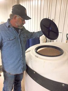 CHESLEY OXENDINE/Muskogee Phoenix  Cane Creek Distillery founder and owner Steve Allen inspects a mash of barley and corn prior to its time in his still.