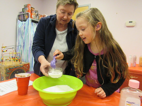 CATHY<br /> SPAULDING/<br /> Muskogee Phoenix<br /> Tamara Henson of Fort Gibson helps her 5-year-old granddaughter, Jenna Henson, scoop sugar to make sugar facial scrub. The two made the scrub at Q.B. Boydstun Library's Christmas Open House last Thursday.