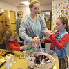 McKinley McCormick, 5, left, and 2-year-old McKeon McCormick, center, reach their glasses toward the punch bowl as their mother, Mikayla McCormick serves punch to McKenzie McCormick, 7. The family enjoyed punch, cookies and other refreshments at Q.B. Boydstun Library's Christmas Open House.
