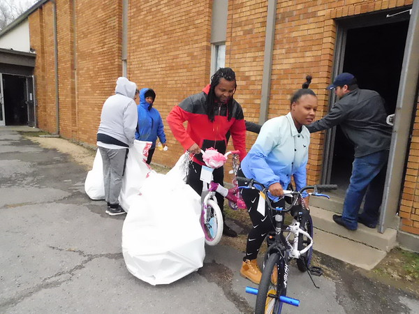 "KENTON BROOKS/Muskogee Phoenix<br /> Chasey Forney, left, and his wife Anissa Spriggs walk out bicycles Tuesday from the Salvation Army Office that will be given to their children, 8-year-old Nyzer and 6-year-old Nazyia for Christmas. The Salvation Army held its Angel Tree distribution Tuesday, and it will continue Wednesday and Thursday. ""God is good,"" Forney said."