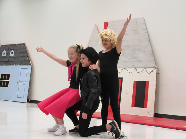 """Staff photo by Cathy Spaulding<br /> Dancers, from left, Turner Trout, Emma Martin and Kristjan Cantrel finish routines from """"Grease"""" for Intermediate Elementary School's variety show."""