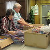 CATHY SPAULDING/Muskogee Phoenix<br /> Volunteers, from left, Joy Walker, Brian Crosby and Linda Willerton unpack coloring kits to distribute for Angel Tree recipients on Tuesday. Scores of people picked up Angel Tree gifts at the Salvation Army.