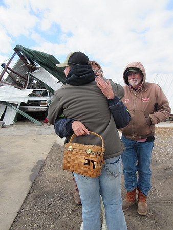 Sue Smith, co-owner of Sue's Recycling and Sanitation, hugs grandson Kreighton Rogers after he gave her a basket of keys recovered from a Friday tornado. The tornado destroyed buildings at the Blackgum area<br /> recycling center. Co-owner Jimmy Smith looks on.
