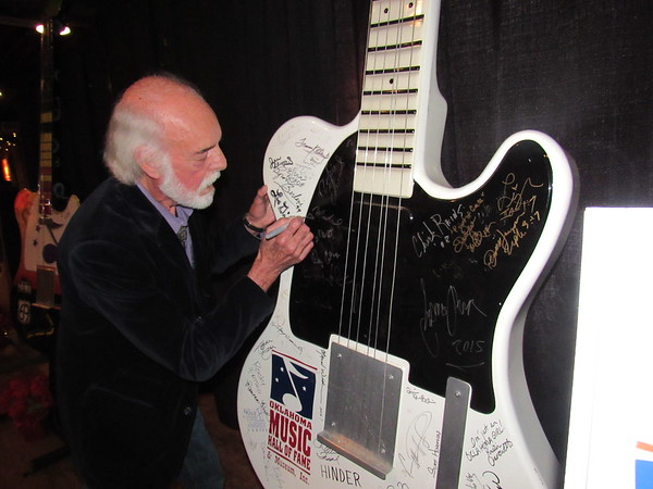 CATHY SPAULDING/Muskogee Phoenix<br /> Folk singer/songwriter Michael Brewer adds his signature to those of past Oklahoma Music Hall of Fame inductees. He was inducted into OMHOF on Saturday before a concert.