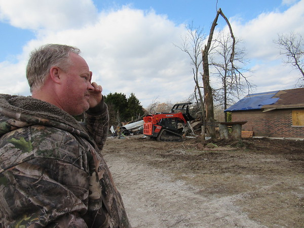 John Brockman, Vian High School baseball coach, surveys damage to his house and adjacent garage caused by a Friday night tornado.