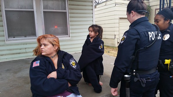Staff photo by Cathy Spaulding<br /> Annabell Tafoya, left, and her 3-year-old daughter Ashley wear police jackets after escaping a Tuesday midday fire at their home on Lawrence Street. Tafoya said three other children were at school.