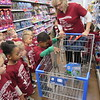 CATHY SPAULDING/Muskogee Phoenix<br /> Early Childhood pupils, front row, from left, Makenna Reynolds, Kayla Newton and others watch classmate Nick Gaulden drop a gift into teacher Jana Dunlap's shopping cart during a trip to buy gifts on Wednesday for needy children. Seven classes bought Angel gifts at Wal-Mart, two classes brought food to the Gospel Rescue Mission and eight classes sang carols and gave gifts at Muskogee nursing homes.