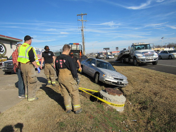"""Staff photo by Cathy Spaulding<br /> Muskogee Fire Department personnel put yellow tape around a manhole after it was struck Thursday morning by a Honda Accord. The Accord had struck a Volvo station wagon. <br /> Muskogee Police Officer Matt Perryman said the northbound Volvo station wagon driven by Sandra Hill was crossing into the J & E parking lot, 1509 N. Main St., when it was struck by a 1996 Honda Accord. Perryman said the Accord driver left the scene. J & E owner Ed Johnson said the driver of the Honda """"came highballing down Main, 60 miles an hour."""" He said the<br /> Honda bounced two feet after hitting a manhole that extended from a ditch. """"Then he runs up here cussing a blue streak,"""" Johnson said about the Honda driver, adding that the driver ran away. Johnson said Hill did not complain about any injuries from the accident."""