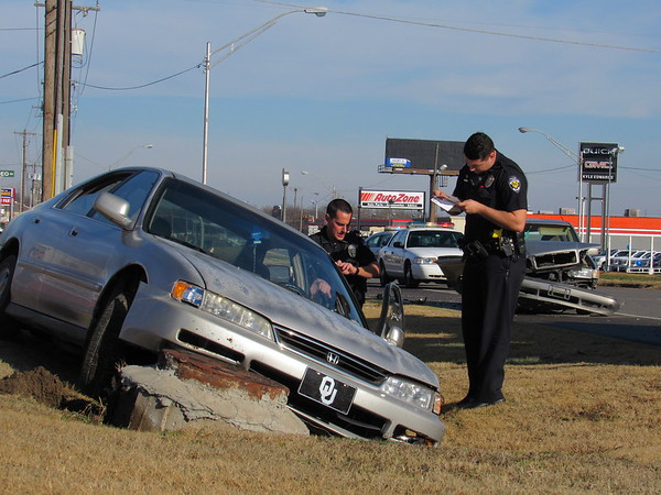 Staff photo by Cathy Spaulding<br /> Muskogee Police officers inspect a Honda Accord after it was involved in an accident with a Volvo station wagon Thursday morning at the 1500 block of North Main Street.