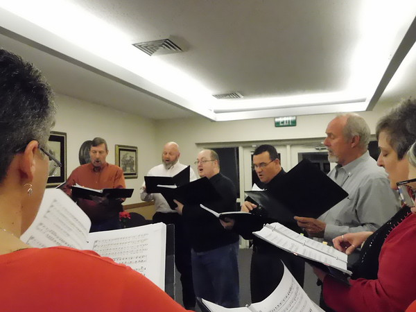 KENTON BROOKS/Muskogee Phoenix<br /> Members of Muskogee Okiepella warm up before the start of Eddie Yadon's Christmas Extravaganza at Church of Jesus Christ of Latter-day Saints. Yadon, third from right, organized the event, which marked its 36th year of Christmas music and songs.