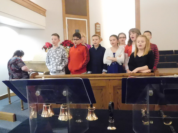 """KENTON BROOKS/Muskogee Phoenix<br /> Children from Muskogee Ward Primary sing """"Jingle Bells"""" with Sara Rawlings playing piano at the 36th annual Night of Christmas Music or Eddie Yadon's Christmas Extravaganza at the Church of Jesus Christ of Latter-day Saints on Saturday night. The event drew singers and musicians of all kinds for the community."""