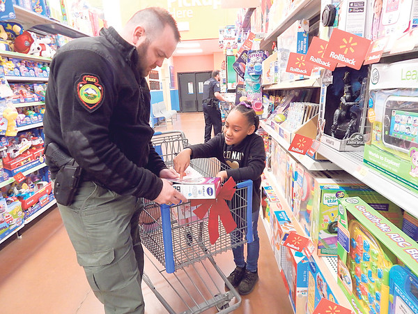KENTON BROOKS/Muskogee Phoenix<br /> Genesis Diaz, 8, points out something in a new toy she wants to get as part of the annual McIntosh County Law Enforcement's Shop with a Cop event at the Checotah Wal-Mart. Children get to pick out and take home $200 worth of toys and $100 in clothing from Sharpe's Department Store.