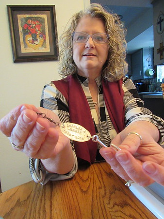 Staff photo by Cathy Spaulding<br /> Janet Bowen shows some stamping work she did on a gift.