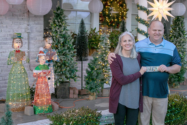 """SHANE KEETER/Special to the Phoenix<br /> Davey and Donna Johnston stand in front of their house on Georgia Avenue holding a $100 bill, first prize in the annual Muskogee Phoenix """"Deck the House Holiday Lights Contest."""""""