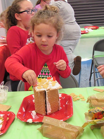 Staff photo by Cathy Spaulding<br /> McKinley McCormick, 4, decorates the roof of the graham cracker  house she built Thursday afternoon at Q.B. Boydstun Library.