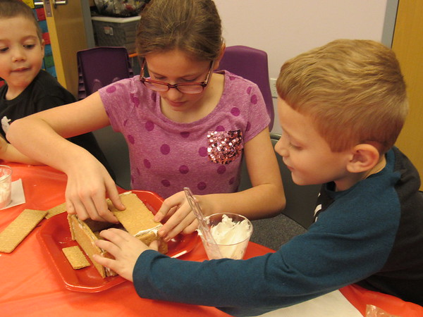 Staff photos by Cathy Spaulding<br /> Kaitlyn Burris, 11, helps 6-year-old Tristan Reynolds put a roof on his graham cracker house. Samuel Reynolds watches how it is done.