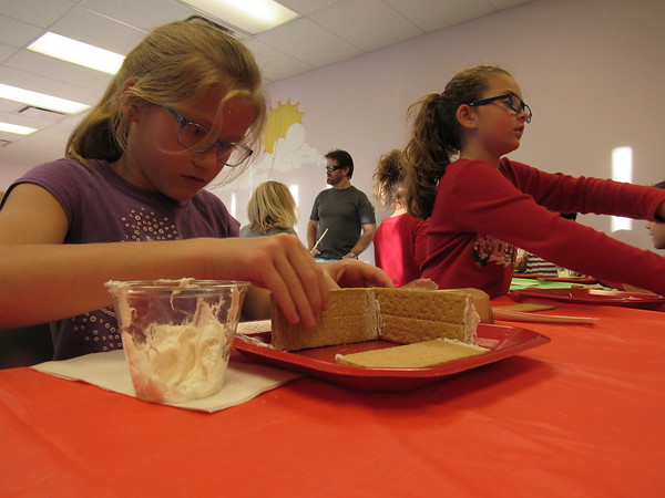 Staff photo by Cathy Spaulding<br /> Makenna Burris, 7, carefully aligns walls of the graham cracker house she built at Q.B. Boydstun Library on Thursday.