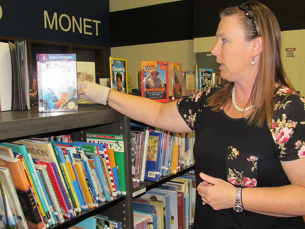 Staff photo by Cathy Spaulding<br /> Sadler Arts Academy library media specialist Amanda Cumbey adjusts a book about Dr. Seuss on the shelf. The book is among 150 biographies Cumbey obtained.