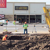 An excavator pulls up mud while workers with H&G Paving contractors work on a hole under 24th Street, just north of Okmulgee Avenue.