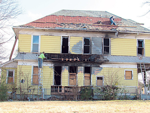CATHY SPAULDING/Muskogee Phoenix<br /> Men do renovations and roof work on a Callahan Street house on Friday. Workers are remodeling an old vacant house at F and Callahan streets.