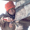 Frederick Mallonnee scrapes a wood beam while helping renovate a house Friday.