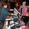 Staff photo by Mike Elswick<br /> Luke Ennis, 6, center, looks over a selection of fireworks at The Castle of Muskogee. The location is one of a variety of locations in the area where fireworks can be purchased. He is seen with Melisa Cross, left, floor manager for the fireworks department, and Melissa Ennis, right, his mother.