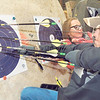 KENTON BROOKS/Muskogee Phoenix<br /> Wade Treadwell, right, of Gore, pulls his arrows from the target after he shoots during one of 12 rounds of competition at the Muskogee County 4-H Archery Shoot at Hatbox on Saturday. Autumn Ingersoll, of Shawnee, stands behind him and also retrieves her arrows from a target.