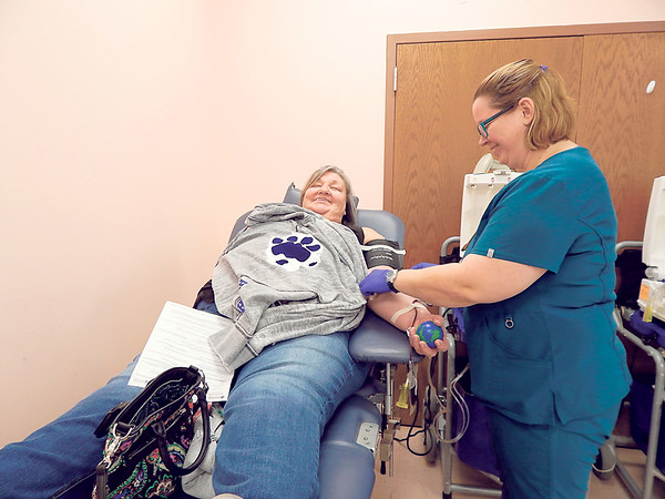 KENTON BROOKS/Muskogee Phoenix<br /> Laverne Mahan of Checotah donates blood at the Checotah High School's student council blood drive this past week at the Checotah Senior Citizen and Community Center. Phlebotomist Jennifer Myhre of the Oklahoma Blood Institute of Tulsa monitors Mahan as she donates.