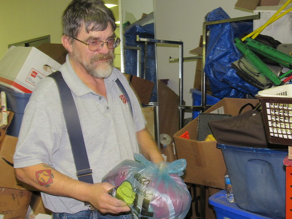 Tim Katowich sorts through storage buckets in the Salvation Army Thrift Store warehouse, where he works part time.