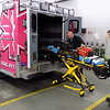 Staff photo by Mike Elswick<br /> James Garvin, left,  paramedic, and Tanner Enger, emergency medical technician, work with a stretcher going into the newest Muskogee County EMS ambulance decked out in pink markings to bring awareness to breast cancer.