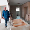 CATHY SPAULDING/Muskogee Phoenix<br /> Dorian Steeber stands between the kitchen and living room of one of his houses damaged in late May flooding. He said he expects kitchen cabinets to be completed this week.
