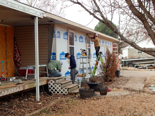 CATHY SPAULDING/Muskogee Phoenix<br /> Workers with Horton Home Solution work on the exterior of the Martinez home on Manard Bayou. Rodger Martinez said his family has not returned home since the house was damaged in late May floods.
