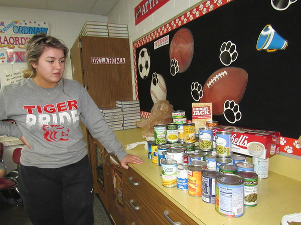 CATHY SPAULDING/Muskogee Phoenix<br /> Fort Gibson High School Student Council President Simone Daniels looks at cans one class collected so far for the school's canned food drive.