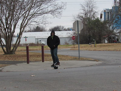 CATHY SPAULDING/Muskogee Phoenix O'Neal Bunch prepares to cross Park Drive in Spaulding Park on his one-wheeled electric skateboard shortly after lunch on Monday. O'Neal Bunch enjoys wheeling around town on an electric skateboard. He is active in the Facebook forum Muskogee Electric Skateboarding.