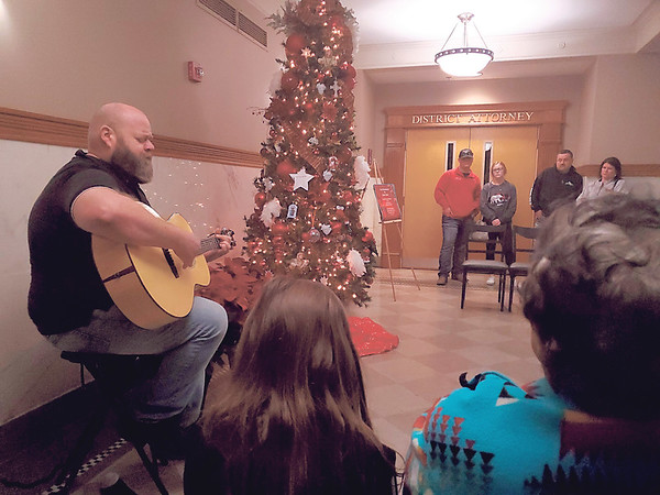 "CHESLEY OXENDINE/Muskogee Phoenix Musician Billy Arnett plays ""Stones Under Rushing Water"" for the gathered audience at the Tree of Remembrance ceremony held Tuesday night in the Muskogee County Courthouse. The event was held in memory of murder victims."