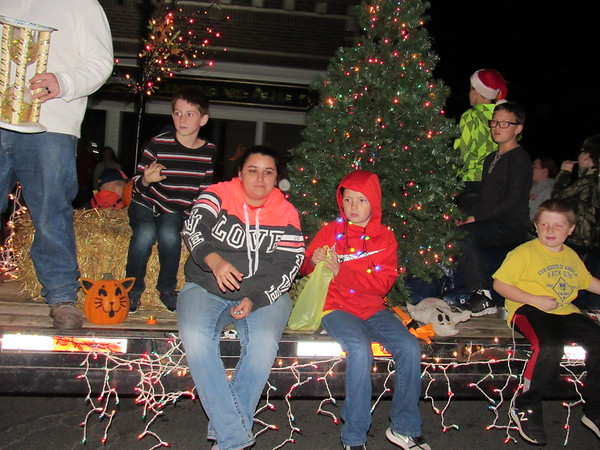 """Staff photo by Cathy Spaulding<br /> Riders on a Cub Scout float toss candy during Fort Gibson's Christmas parade Monday night. The float featured Halloween decorations along with a Christmas tree to reflect the parade theme """"Father Time."""""""