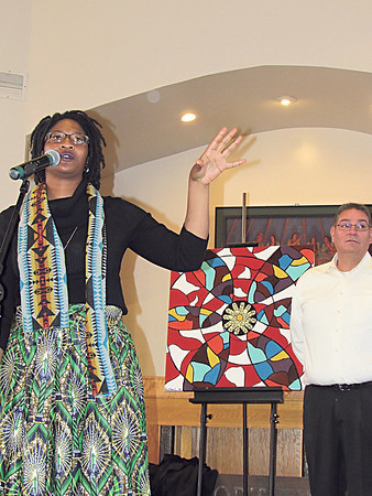 CATHY SPAULDING/Muskogee Phoenix<br /> Bacone College graduate Kristian Lake discusses the painting she created recalling a rose window that was part of Bacone College Chapel before it burned in 1990. The painting will hang over the chapel altar. Bacone Art Department Chairman Gerald Cournoyer stands by the painting.