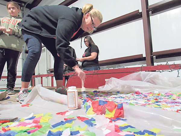 St. Joseph Catholic School preschool teacher Michelle Olshen paints Modge Podge onto tissue paper pieces while helping students build the float for the Muskogee Christmas parade.