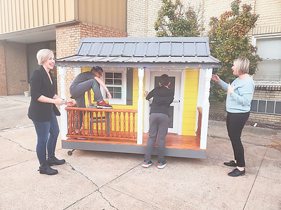CHESLEY OXENDINE/Muskogee Phoenix From left, Stacy, Archer and Stockton Hogle, joined by Holly Rosser-Miller, check out a handcrafted playhouse built by Dr. Larry Hamilton for the Third Annual Kids' Space Charity Auction.