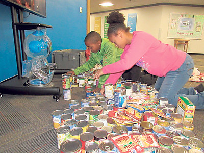 CATHY SPAULDING/Muskogee Phoenix Ben Franklin STEM Academy Student Council President Michael Puckett, left and classmate D'Mya Brown set up a small portion cans they collected in the school's can drive. They already doubled their goal of collecting 500 cans.