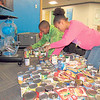 CATHY SPAULDING/Muskogee Phoenix<br /> Ben Franklin STEM Academy Student Council President Michael Puckett, left and classmate D'Mya Brown set up a small portion cans they collected in the school's can drive. They already doubled their goal of collecting 500 cans.