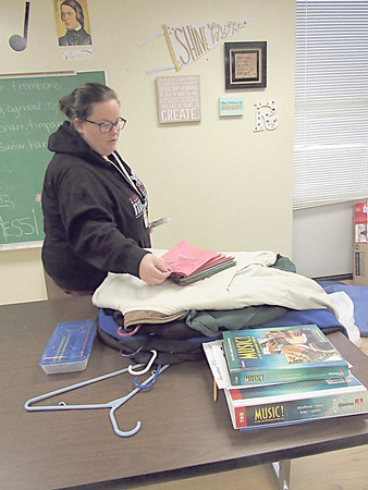 Hilldale High School leadership class teacher Brittany Stoddard sorts through Christmas cards students made and coats they collected for a clothing drive. The class also is collecting new blankets and socks for nursing home residents.