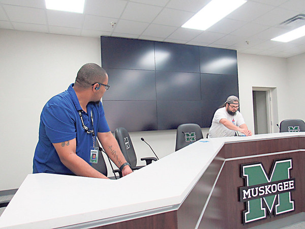 CATHY SPAULDING/Muskogee Phoenix<br /> Muskogee Public Schools Director of Maintenance Odell Alexander, left and MPS lead painter Norberto Garcia make finishing touches on the new MPS board of education dais. Behind them is a new digital screen.