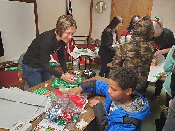 CHESLEY OXENDINE/Muskogee Phoenix<br /> Presbyterian Church volunteer Rebecca Grant helps 10-year-old Dion Gillima wrap a present for his grandfather.
