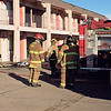 Staff photo by Mike Elswick<br /> Muskogee Fire Department firefighters stand near a pile of burnt clothing and personal effects removed from a room at the Royal Inn after an overheated electrical cord set clothing on fire. No injuries were reported, but the retired couple living in the room said they lost nearly all their personal items in the fire.