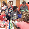 WENDY BURTON/Special to the Phoenix<br /> Kody Maxwell, 5, volunteer Elaine Brownell, James Blackshear, 7, Jabez Blackshear, 4, and volunteer Rick Riggs wrap gifts at the Joy of Giving Shoppe.