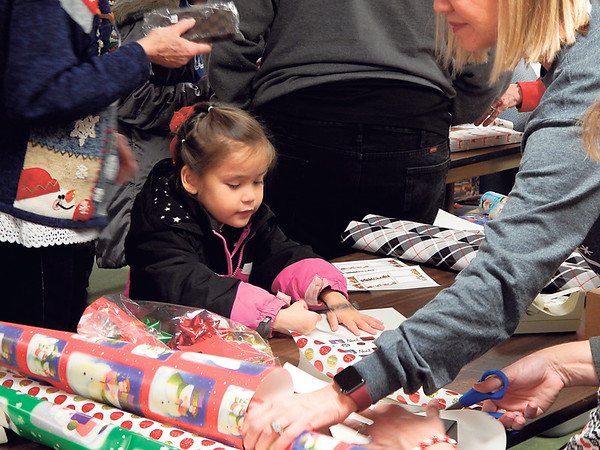 Izabella Maxwell, 5, wraps gifts for her mom and dad at the Presbyterian Church of Muskogee's Joy of Giving Shoppe.